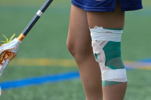 Taped left knee of female lacrosse player signifies the injuries prospective student-athletes play with to showcase for college coaches at the Nike Elite G8 girls lacrosse club tournament (2015) which is part of the early recruiting process.