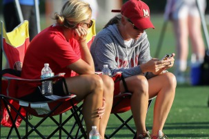 Maryland women's lacrosse coaches are sitting in their chairs texting on phone as they watch prospective student-athletes at a club tournament for girls lacrosse as part of the early recruiting process.
