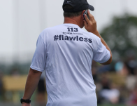 Ricky Fried, Head Georgetown Women's Lacrosse coach, speaks on his cell phone about recruiting at a showcase tournament of early recruits (2015).  © Equity IX - SportsOgram - Photo by Leigh Ernst Friestedt