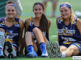 Three teenage girls (Yellow Jackets Club Lacrosse team) sit on the ground and rest after playing lacrosse games at showcase tournament for college coaches - early recruiting. © Equity IX - SportsOgram - Photo by Leigh Ernst Friestedt