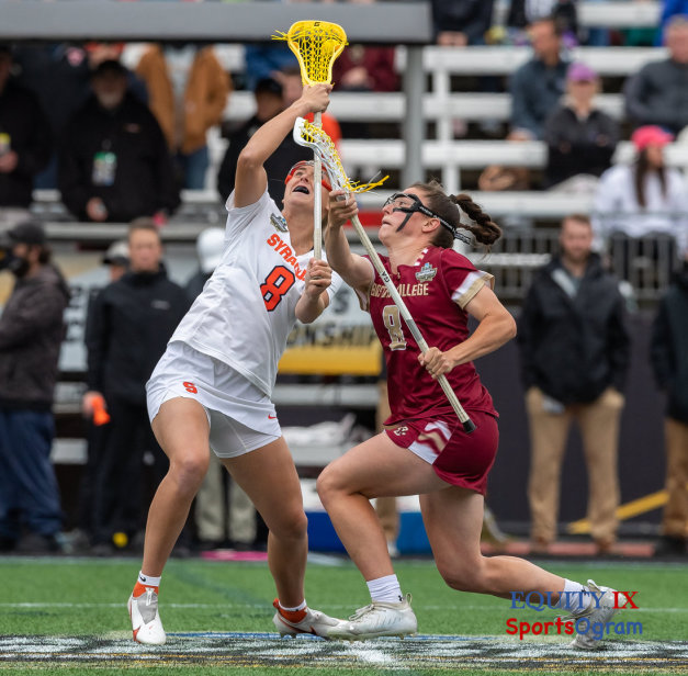 #8 Charlotte North draws against Syracuse #8 center to start 2021 NCAA Women's Lacrosse Championship Game - yellow lacrosse ball is between the two lacrosse sticks and being drawn into the air © Equity IX - SportsOgram - Leigh Ernst Friestedt