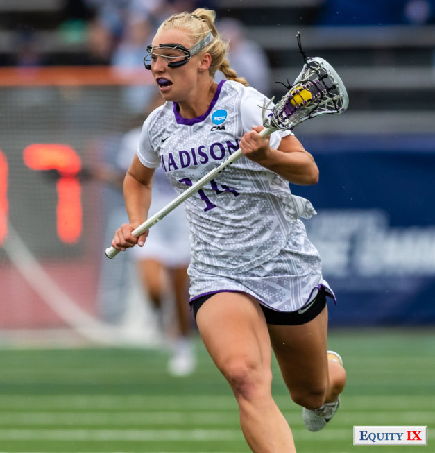 #14 JMU midfielder cradles yellow lacrosse ball left handed wearing goggles and a purple mouthguard at 2018 NCAA Women's Lacrosse Championship Game vs Boston College © Equity IX - SportsOgram - Leigh Ernst Friestedt