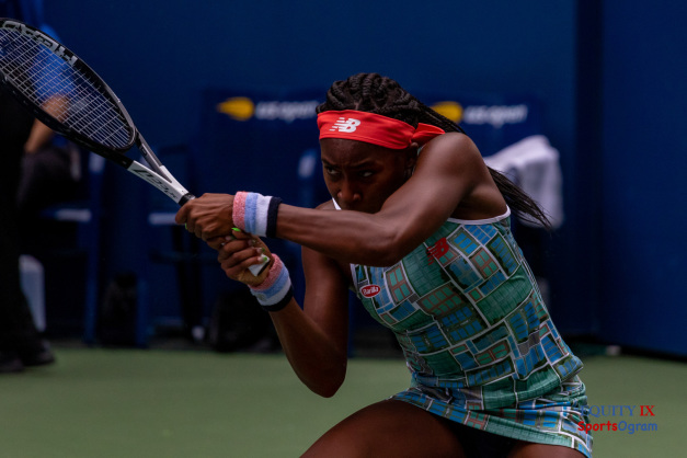 Coco Gauff hits a ton handed left backhand in a multi-colored tennis dress with a red New Balance headband and Head tennis racket at US Open Tennis Championship © Equity IX - SportsOgram - Leigh Ernst Friestedt