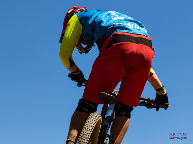 Mountain biker jumps in the air wearing red shorts and bright blue and yellow jersey with red helmet at mountain bike race at Lake Tahoe © Equity IX - SportsOgram - Leigh Ernst Friestedt